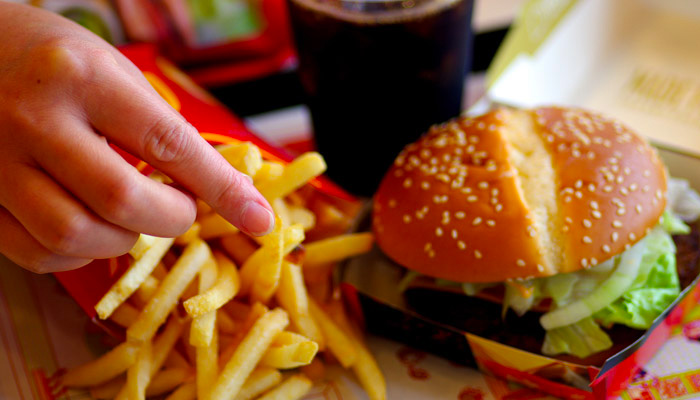 hand-reaching-for-fries-and-burger